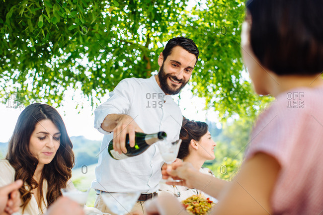 Man pouring champagne during a meal outdoors with friends