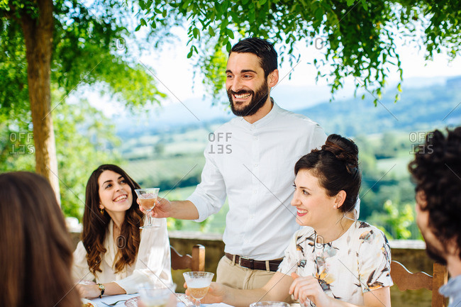 Group of friends having meal together, outdoors, man holding champagne glass, making toast