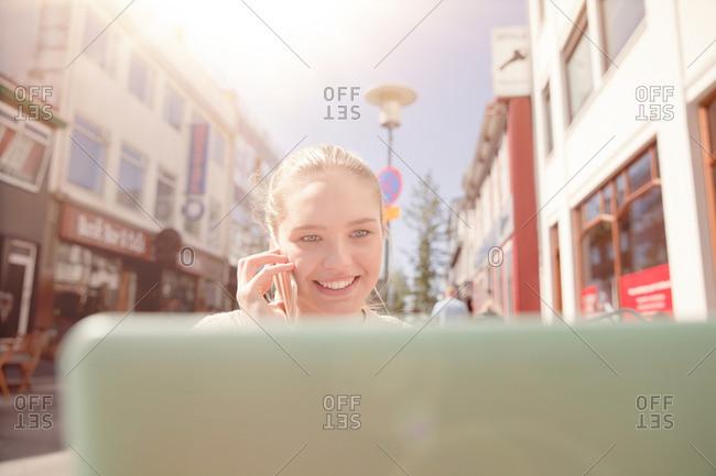 Teenage girl sitting outdoors using laptop computer, talking on cellular phone, Reykjavik, Iceland