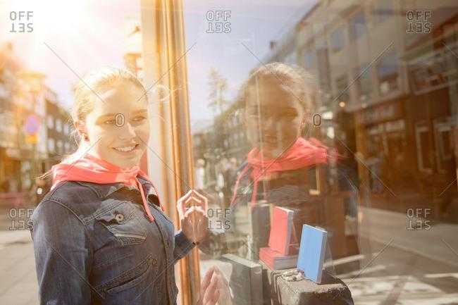 Teenage girl window shopping smiling, reflection in window of shop fronts, Reykjavik, Iceland