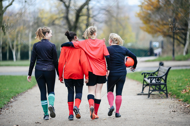 Rear view of female soccer players en route to play soccer in park