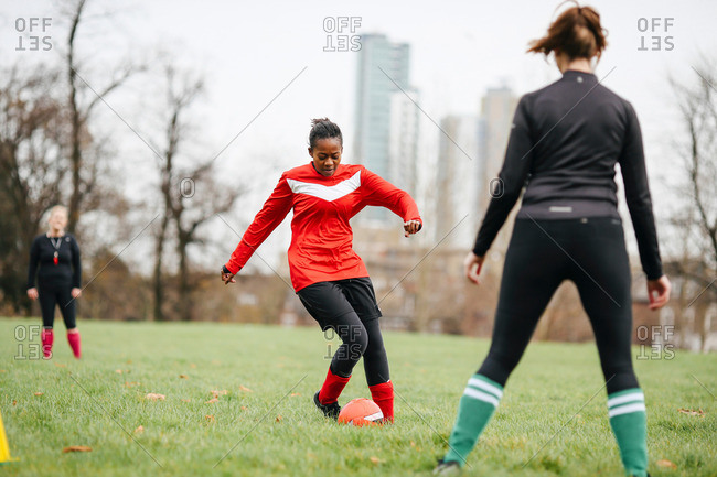 Female soccer player practicing with soccer in park