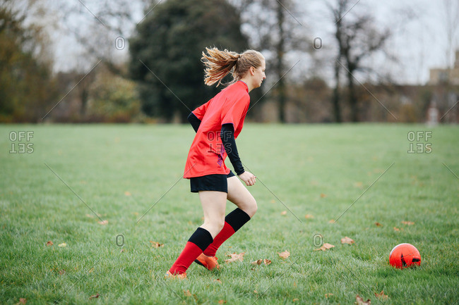 Teenage female soccer player practicing with soccer ball in park