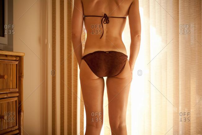 Woman in bikini in hotel room, rear view