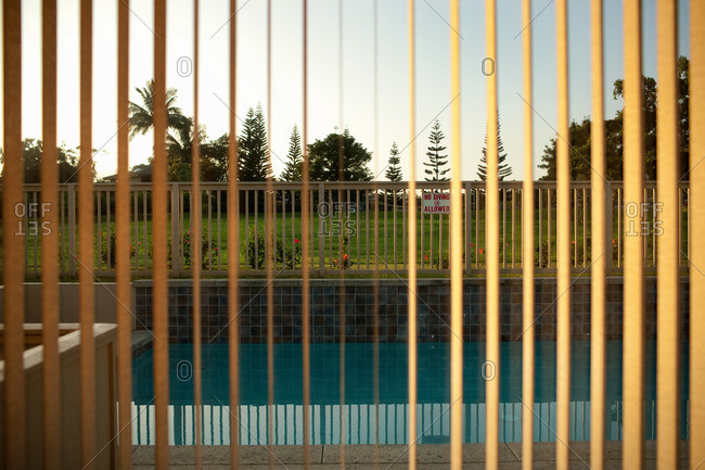 View of swimming pool through window blinds