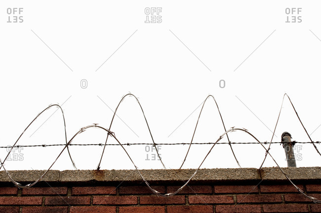 Razor wire on top of brick wall