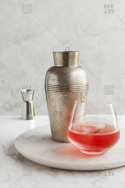 Cocktail shaker and negroni cocktail on a marble lazy susan