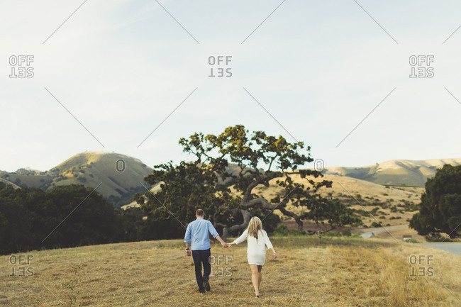 Couple walking hand-in-hand through a rural meadow