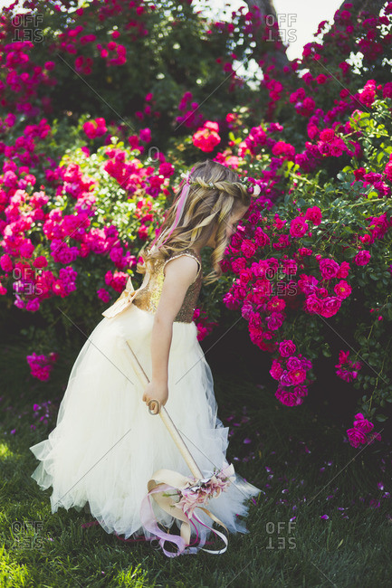 Girl dressed like a princess smelling flowers in a garden