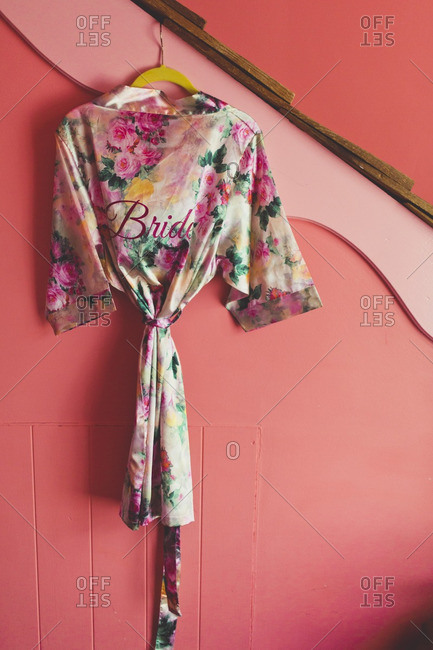 Satin floral robe embroidered with the word \'bride\' hanging on a pink wall