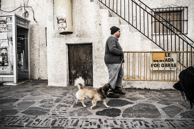 Andalusia, Spain - July 6, 2015: Dog and owner at Pampaneira, La Alpujarra, Andalusia, Spain