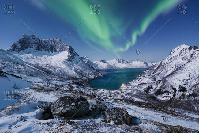 Northern light over snow covered mountains in Norway