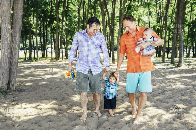 Homosexual couple walking with sons on beach