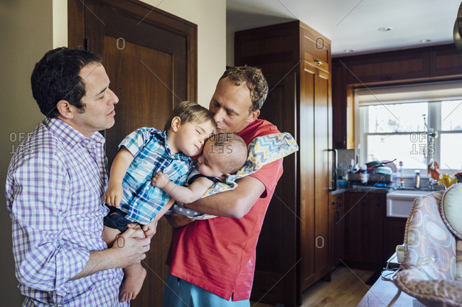 Homosexual couple holding sons at home