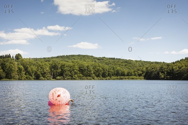 Person sitting with umbrella on inflated ring at lake against sky