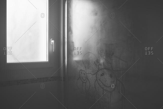 Child's drawings in condensation on glass shower door