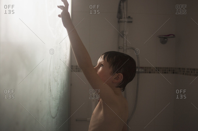 Young boy in shower drawing on glass door