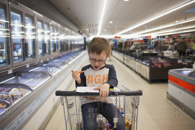 Young boy in shopping cart crosses items off list
