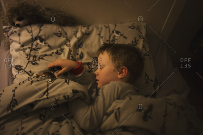 Overhead view of young boy asleep in bed