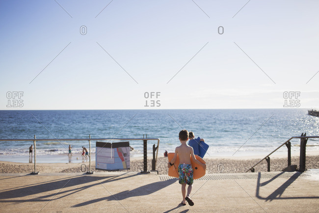 Children carrying boogie boards to beach