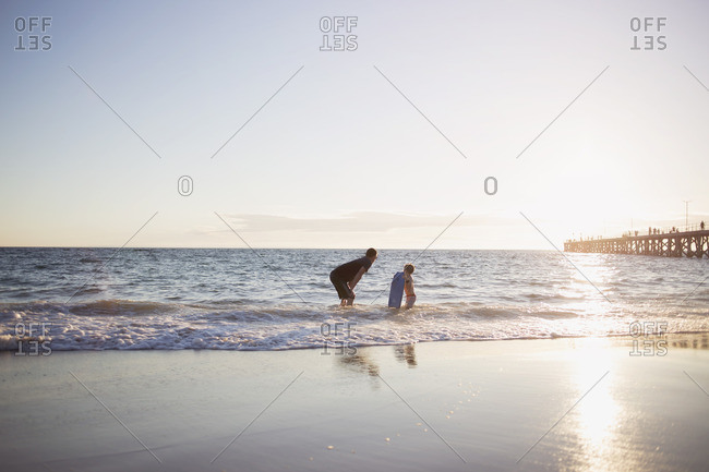 Father and son with boogie board in ocean