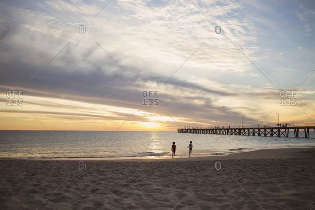 Two children running on beach at dusk