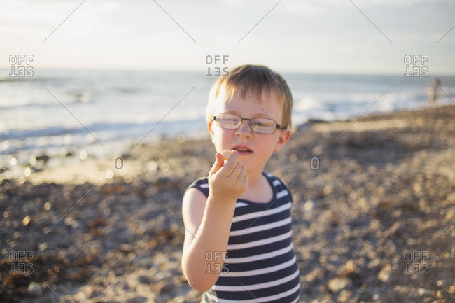 Young boy with glasses examines a beach pebble