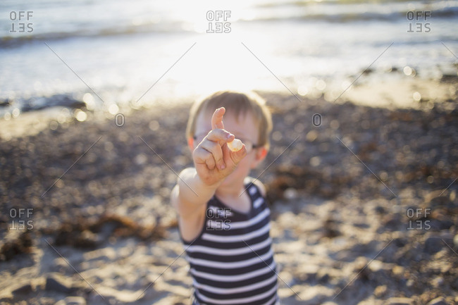Boy with pebble he found on beach