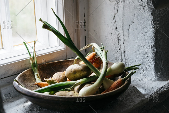 Close-up of root vegetables on rustic kitchen windowsill