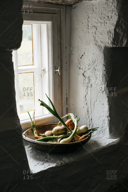 Bowl of root vegetables on rustic kitchen windowsill