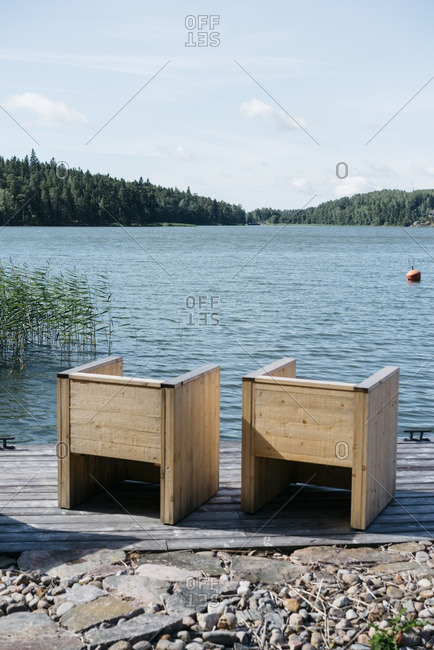 Two wooden seats on deck in Finnish harbor of Baltic Sea