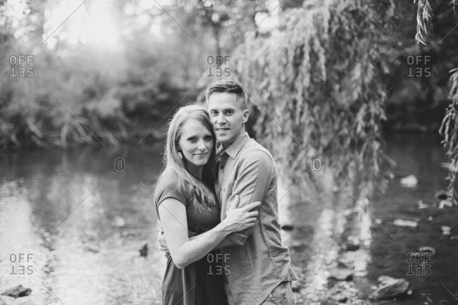 Couple embraced beside a river in black and white