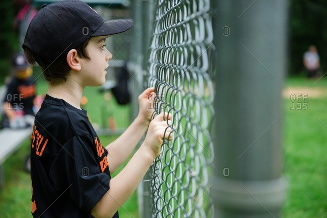 Boy holding onto chain-link fence watching baseball game