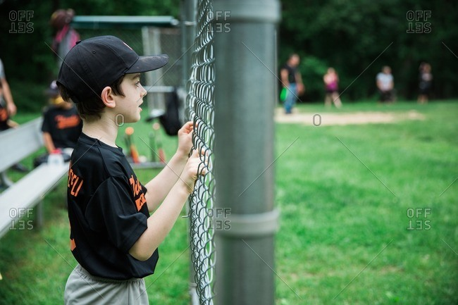 Boy watching baseball game through a chain-link fence