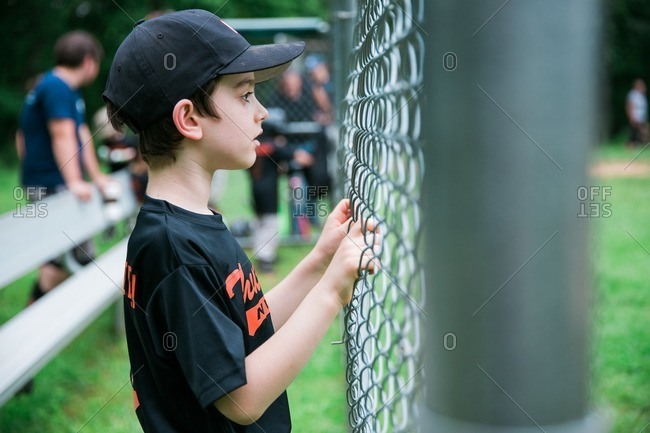 Boy watching baseball game from behind a fence