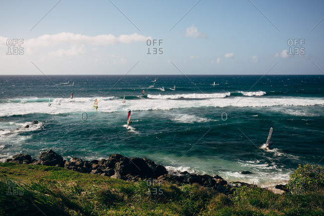 Hawaii, Maui - April 30, 2016: Windsurfers in the ocean near a rocky coast at Maui