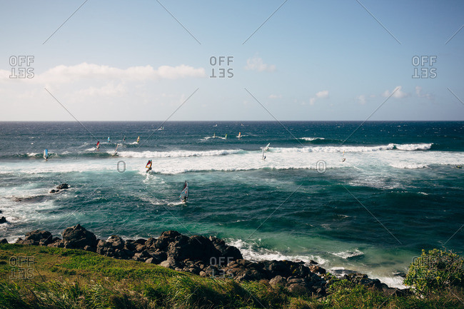 Hawaii, Maui - April 30, 2016: Windsurfers near a rocky beach in the ocean at Maui