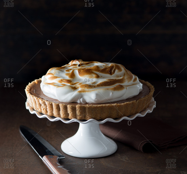 Chocolate pie on a stand topped with meringue