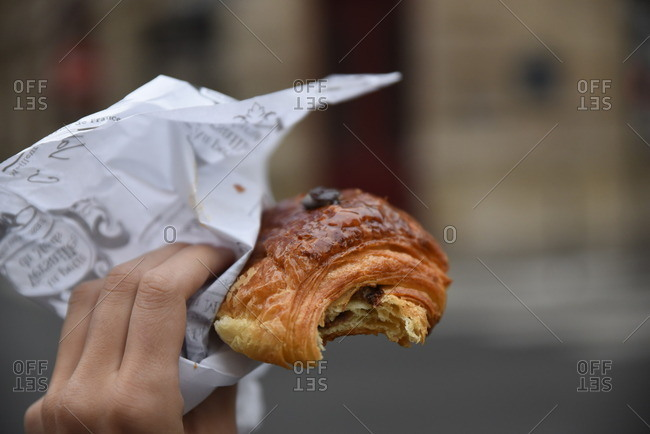 Close-up of a person holding a pastry with a bite missing