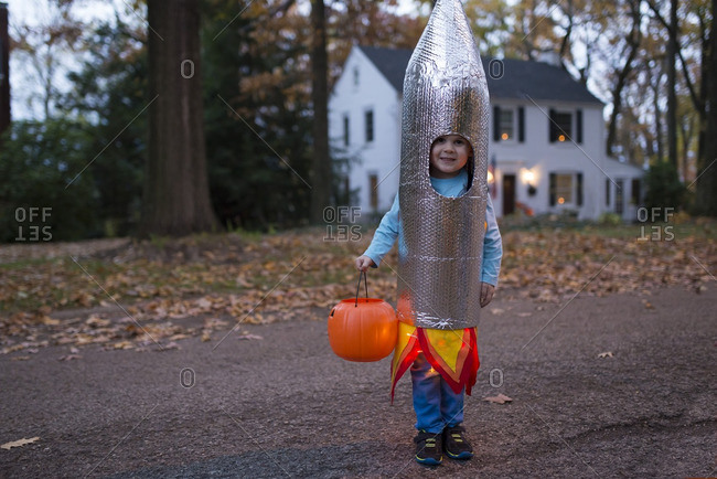 Boy standing on a suburban street wearing a rocket Halloween costume