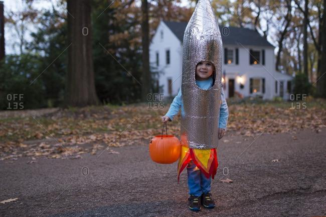 Boy standing on a suburban street wearing a rocket Halloween costume