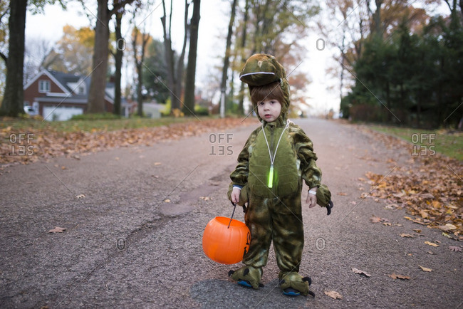 Boy standing on a suburban street wearing a dinosaur Halloween costume