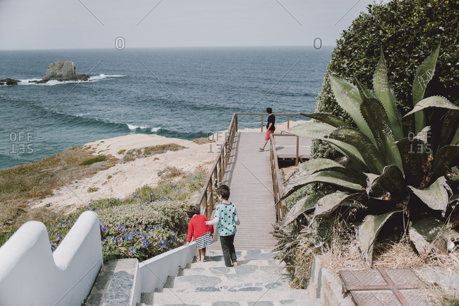 Two children playing together on steps overlooking a scenic beach