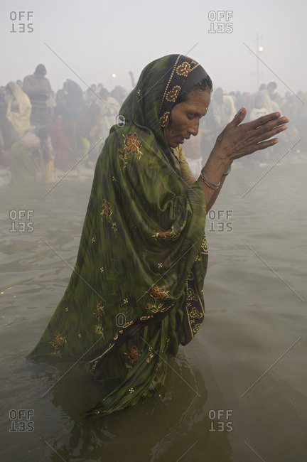 Uttar Pradesh, India - January 26, 2010: A Hindu woman worshiping in the Yamuna river