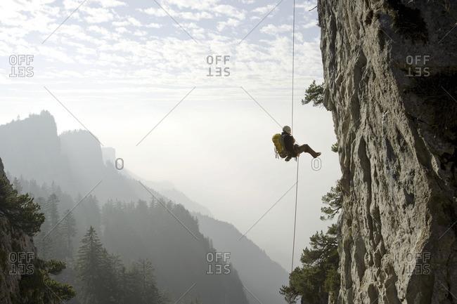 Vorarlberg, Austria - June 15, 2008: Mountaineer descending a cliff