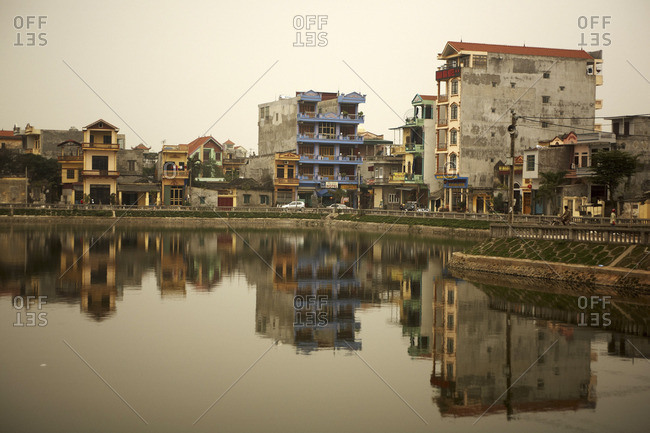 Ninh Binh City, Vietnam - March 15, 2011: City scape reflecting on the river at dusk