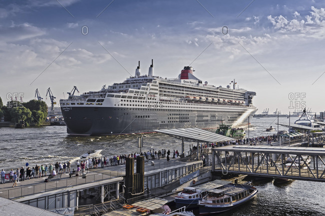 Hamburg, Germany - July 25, 2012: Spectators watching the luxury cruise ship Queen Mary 2 in the harbor of the Northern Elbe in HafenCity