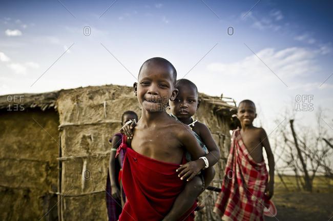 Arusha, Tanzania - November 15, 2012: Children standing outside of a hut