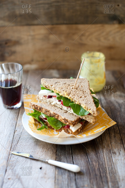Sandwich on a plate served with a glass of black coffee