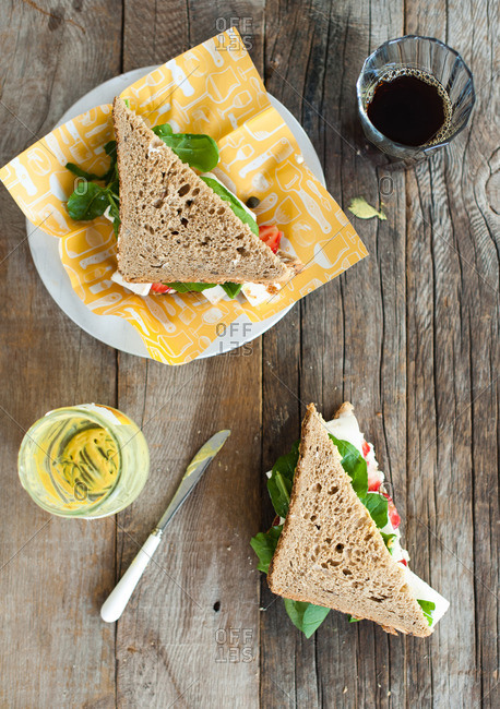 Overhead view of a sandwich on a plate served with a glass of black coffee